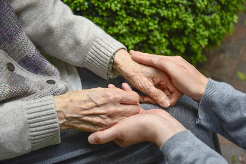 imagen de unas manos cuidando de personas mayores