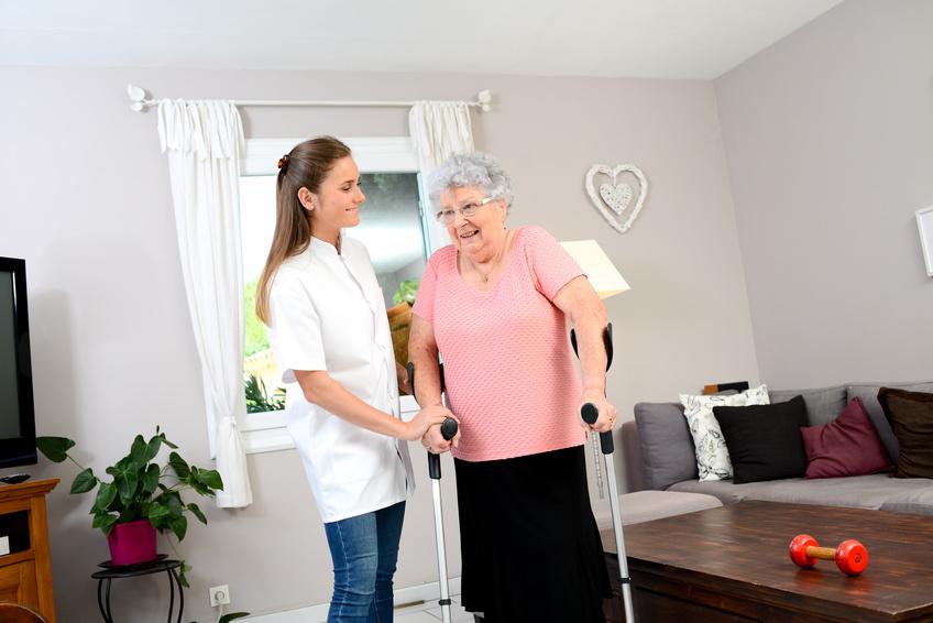 una enfermera a domicilio ayudando a una persona mayor con muletas