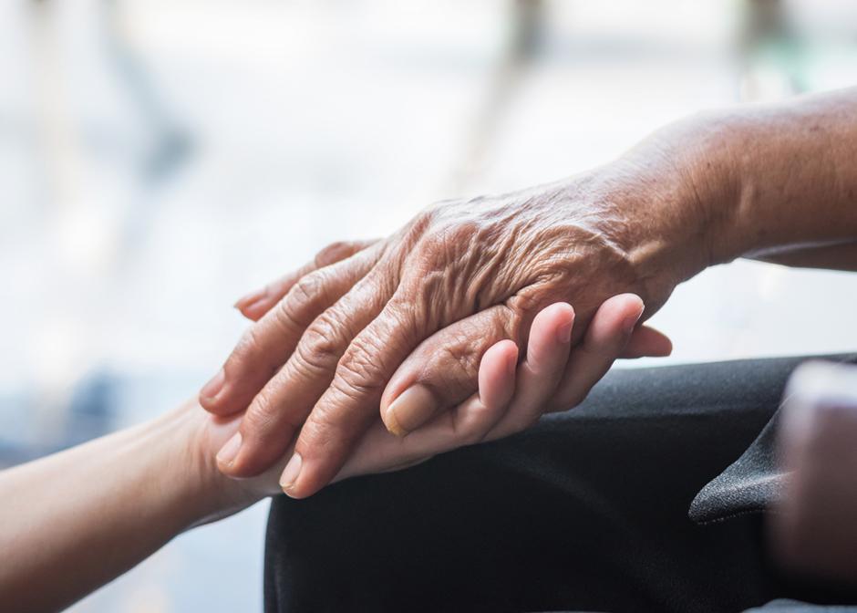 Cuidador a domicilio ayudando a una personas con Parkinson