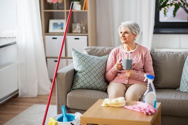 persona mayor en el sofá con productos de limpieza